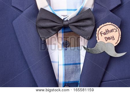 Father's Day badge with mustache. Bow tie on checkered shirt. Gentleman's look for party.