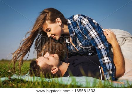 teenagers lie on the green summer grass. girl on top of the guy