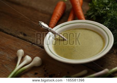 Green Pea Soup In A Ceramic Bowl, Carrots, Onion, Garlic And Herbs. Wooden Background
