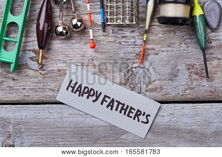 Fishing tackle for father's holiday. Greeting card on wooden backdrop. Leisure for man.