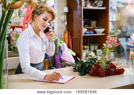 Professional female florist is making notes while talking on phone with customer. She is standing and smiling