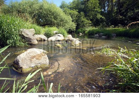 Landscape with clear water in fast small river quickly runs between stones in summer day. horizontal photo