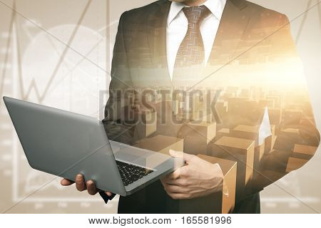 Businessman using laptop in warehouse. Double exposure. Business concept