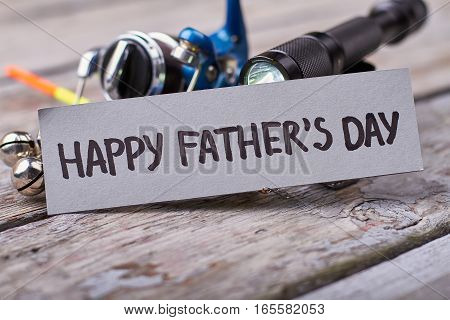 Flashlight and Father's Day card. Fishing tackle on old wood. Modern fishing equipment.