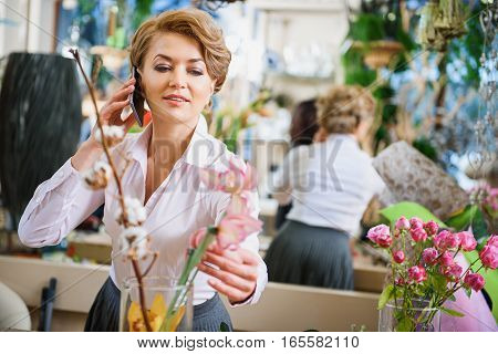Happy woman is talking on mobile phone and smiling. She is standing in shop and touching flower with admiration