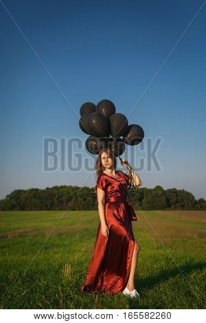 girl in red dress with black balloons standing in a field on the grass