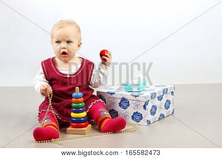 Unhappy angry little baby girl  sitting alone with presents and toys.