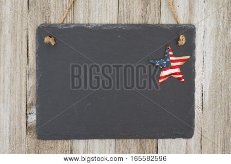 Old fashion patriotic hanging chalkboard background A retro chalkboard with a vintage USA star hanging on weathered wood background with copy space for your message