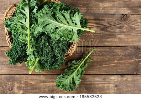 Top view of freshly harvested kale in a wicker basket on a rustic wooden background with copy space.