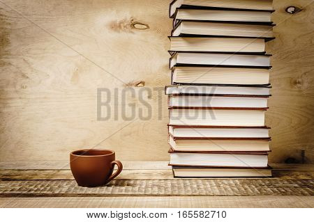 pile of old books and tea on a wooden shelf