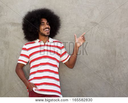 Smiling Man By Wall With Hand Outstretched Pointing Finger