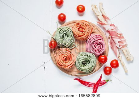Colorful rolled pasta cherry tomatoes and bacon on the white wooden background.