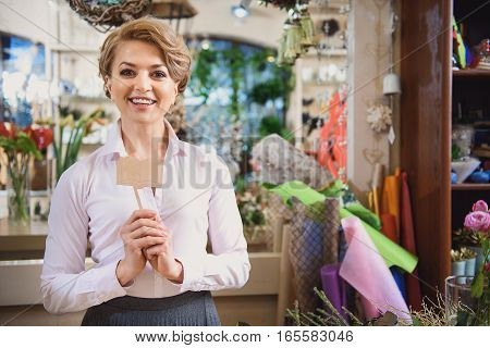 Joyful female florist is showing wooden figure in shape of book. She is looking at camera and smiling