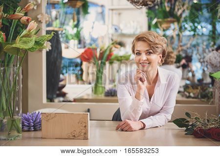 Professional female florist is standing and leaning on counter with relaxation. She is looking at camera and laughing