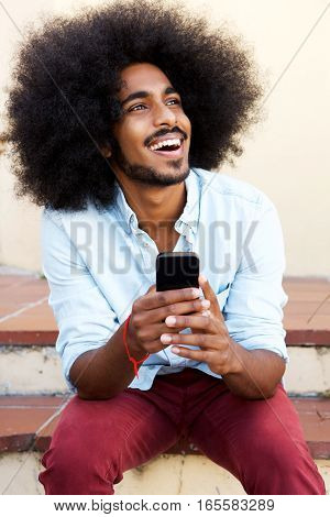 Happy Man Sitting On Steps With Mobile Phone Laughing