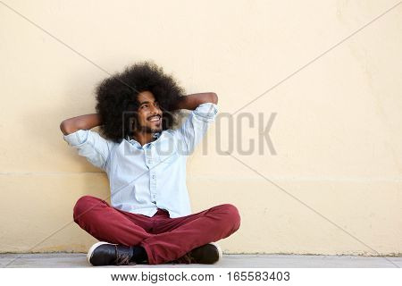 Smiling Man Sitting On Floor Leaning On Wall