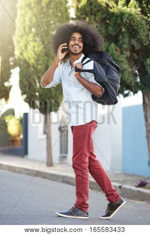 Happy Man Walking Outside With Phone And Bag
