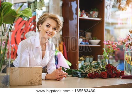 Enjoy our service. Friendly woman is working in flower shop. She is looking forward with smile while standing at table