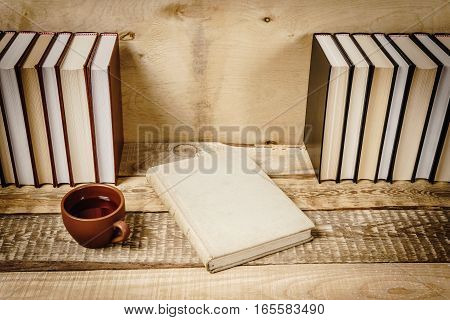 view of the cover of the book and a hot cup of tea on a wooden shelf