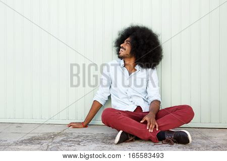 Cheerful Man Sitting Outside On Floor By Wall
