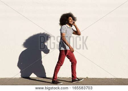 Happy Afro Man Walking Outside With Mobile Phone