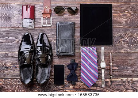 Men's accessories on wooden background. Black shoes and bow tie. Expensive look for man.