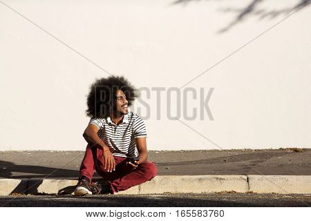 Happy Man Sitting On Sidewalk Outside With Phone