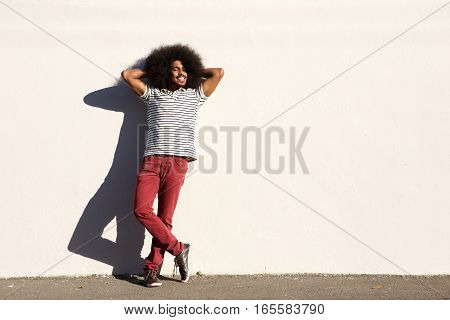 Casual Man Standing Outside With Hands In Hair Relaxed