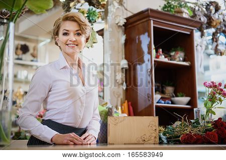 Happy flower shop owner is standing at counter with joy. She is looking forward and laughing