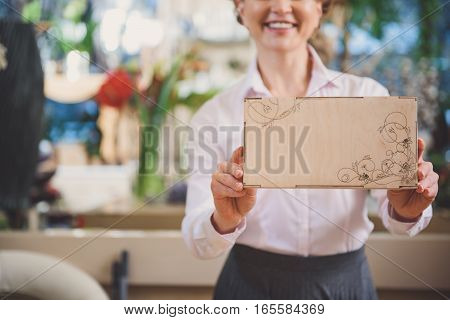 Look at this wonderful wood box with flower pattern. Joyful woman is presenting goods in flower shop and smiling