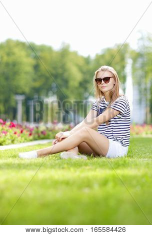 Teenagers Lifestyle Concepts. Caucasian Blond Teenage Girl in Green Summer Park. Vertical Image Orientation