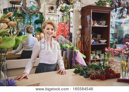 Friendly female florist is working in her own store with enjoyment. She is standing and laughing