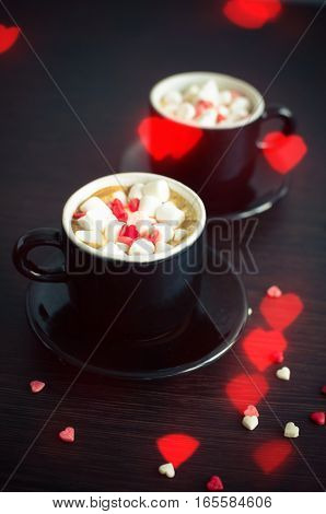 Two cup of coffee with marshmallow and small hearts. Breakfast on Valentine's Day for couple. Romantic love background. Valentines theme. Selective focus.