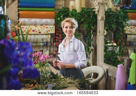 I am ready to make bouquet. Confident woman is holding plant and smiling. She is standing at table in her workshop