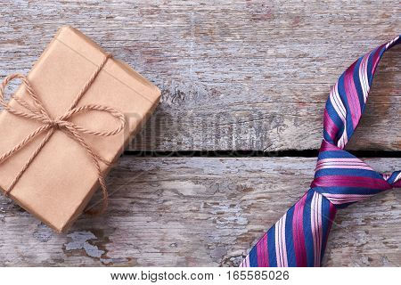 Necktie and wrapped present. Rope bow on gift box. Tie as office symbol.
