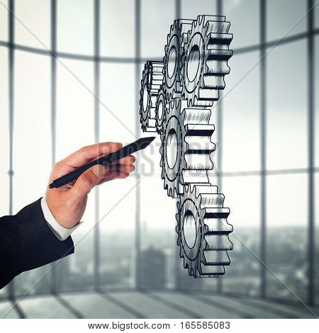 Businessman draws a System of a mechanism gears move together