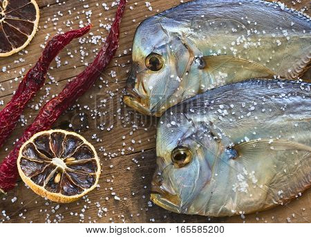 Two fish Cold smoked Vomero. Red pepper. Dried lemon. Are scattered sea salt. On a wooden background. Top view