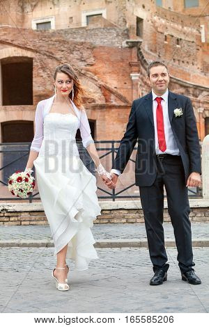 Newlyweds, hands in hands. Happy and joyful married couple in Rome's historic center.