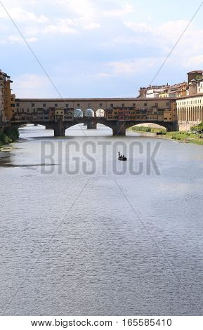 Ancient Bridge called Ponte Vecchio in Florence Italy and a boat in arno river poster