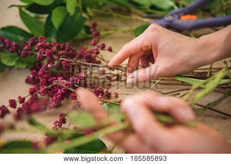 Close up of florist hands joining braches of rowan while making bouquet