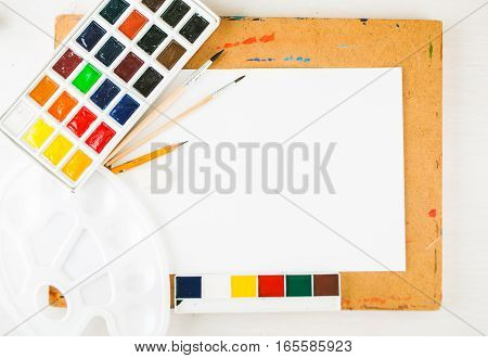 background with watercolor, brashes for artist and white blank for artwork