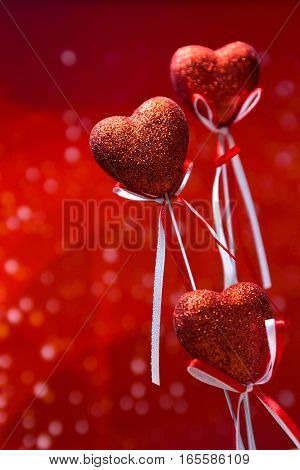 Valentines day. Red hearts on red blurred background closeup with copy space for congratulation