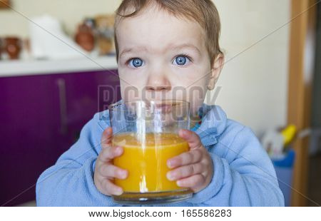 Baby boy drinking a big glass of orange juice fresh made. Education on healthy nutrition for children concept