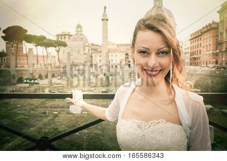 Smiling bride happy for her wedding in the ancient city of Rome Italy. Imperial Forums. The blonde woman wears bridal white dress.