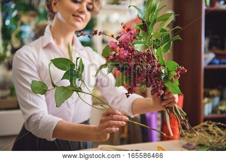 Dreamful woman is making bouquet with joy. She is looking at flowers with admiration and smiling