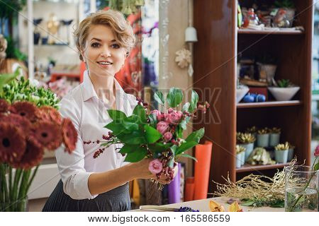 These flowers create magic atmosphere. Joyful female florist is holding bunch of pink roses and smiling