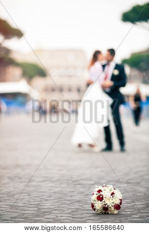 Newlyweds in the city. Bouquet of flowers on the ground on cobblestones. Colosseum. Rome Italy. Selective focus on bouquet of flowers. Couple, husband and wife, just married kissing. Bride and groom.