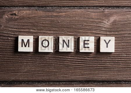 Alphabet letters on wooden pieces collected word money