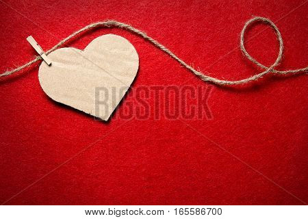 Valentines day. Hearts from felt and cardboard on rope with clothespin on red background
