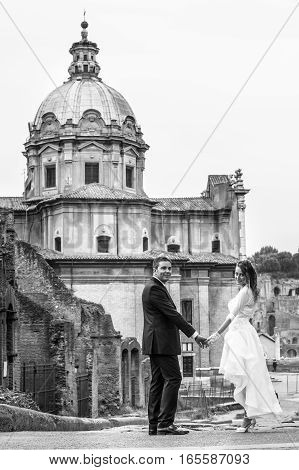 Newlyweds in the city. Happy married couple. Black and white. Husband and wife are in the historic center of Rome, Italy.
